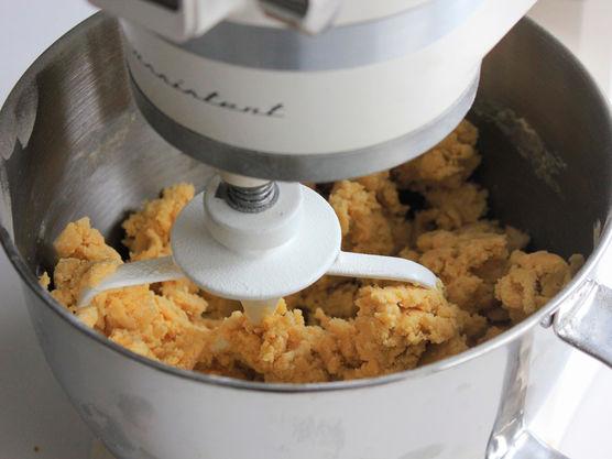 Ha alt det tørre i en kjøkkenmaskin sammen med smøret. Bruk en grind, og kjør til alt er blandet sammen og det ser ut som sand. Tilsett så fløte og eggeplommer, og kjør blandingen i kjøkkenmaskinen til deigen er kommet godt sammen og er blank.