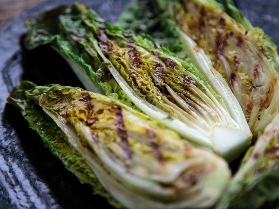 Del hjertesalaten i to på langs, og gni snittflaten med olje, salt og pepper.  Legg salaten med snittsiden ned på grillen, og grill i 2 minutter. Den trenger ikke grilles på begge sider.