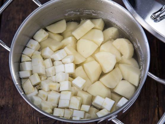 Skrell poteter og sellerirot og skjær i like store terninger. Kok møre i usaltet vann. Hell av vannet og damp poteter og sellerirot godt av.