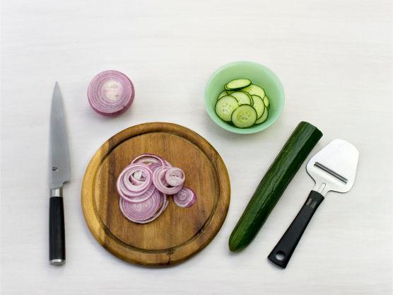 Høvle agurken og skjær løken i tynne skiver i en bolle.