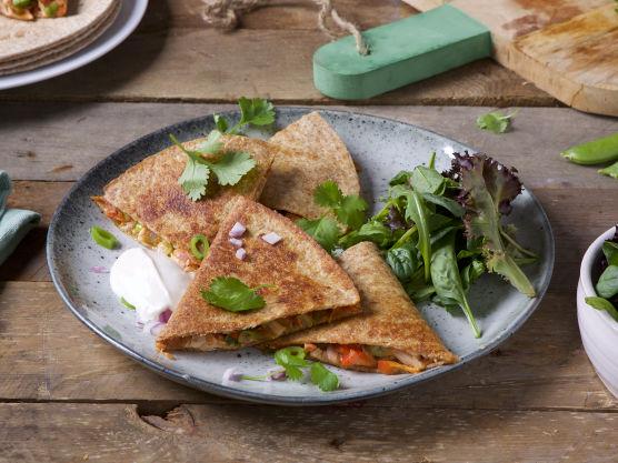 Server Quesedillasene med kesam og frisk grønn salat.