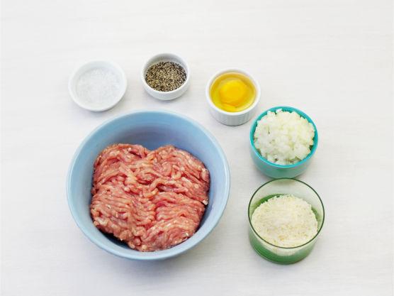 Finhakk løk og riv parmesan. Rør ut kjøttdeig i en bolle med løk, parmesan, egg, salt og pepper.