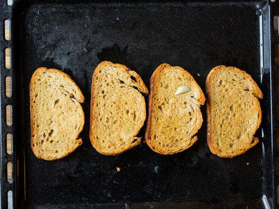 Drypp olivenolje på skivene og stek dem i ovnen til de er gylne. Gni deretter skivene inn med hvitløk.