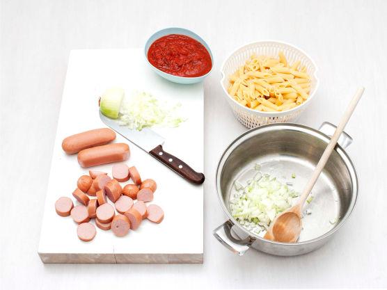 Skjær pølsene i biter. Skrell og hakk løk, og surr løken i olje i en gryte til den er myk. Ha pastasaus, pølser og pasta i gryten og bland godt