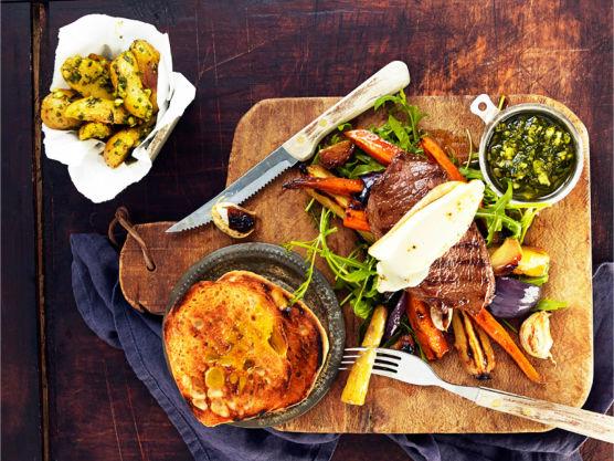 Legg biffene på et stekebrett og osten på toppen. Gratiner biffene under grillelementet i ovnen og anrett i brødet, med litt aioli og pesto ved siden av. Vend de lune grønnsakene med litt pesto og ruccula og server.