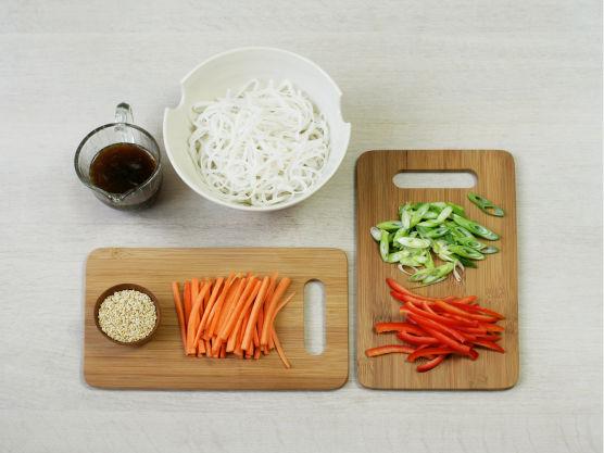 Kok nudlene etter anvisning på pakken og skyll dem i kaldt vann. Skjær grønnsakene i strimler.