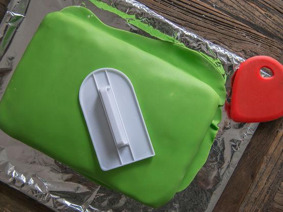 Bruk en smoother for å fjerne luftboblene, og for å få ett jevnere resultat. Start på toppen av kaken, og ta sidene til slutt. Avslutt med å skjære vekk overflødig masse.