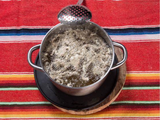 Fritér strimlene i matolje til det slutter å boble rundt kjøttet. De skal være gjennomsprø. Varm opp glaze og vend inn de tørrstekte biffstrimlene rett før servering. Fritér spinaten til den blir mørkegrønn og sprø.