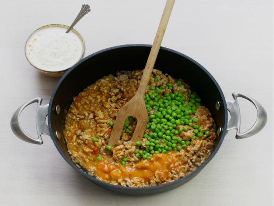 Tilsett kyllingkjøttdeig og stek til den skifter farge. Rør inn saus og erter. La småkoke i ca. 5 min.
