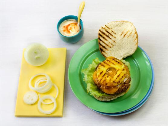 Ha salat og dressing på hamburgerbrødene. Legg på hamburgeren, en ananasring og et par løkringer.