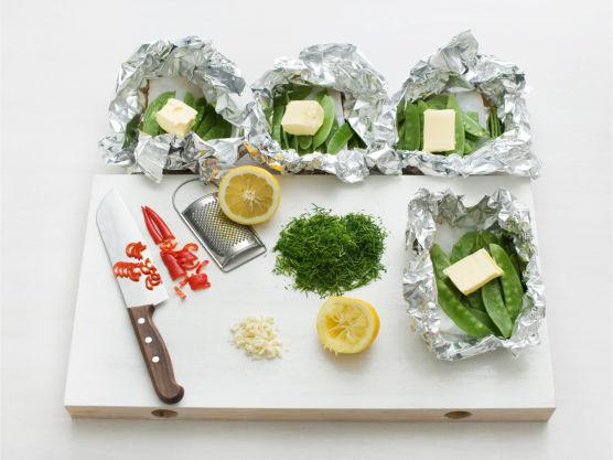 Rens og hakk hvitløk, chili og dill og fordel over fisken. Ha over litt sitronsaft, sitronskall og smør og brett folien i tette pakker.
