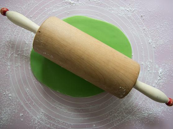 Skjevle ut grønn fondant til den dekker kaken. Kle kaken med grønn fondant.