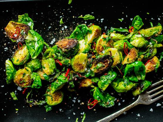 Rens og del rosenkålen i to eller fire. Finsnitt chili og finhakk hvitløken. Varm en stor stekepanne med litt olje. Tilsett rosenkålen og stek den gyllen og knapt mør, ca. 1–2 minutter over høy varme.