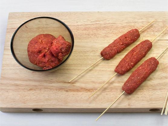 Bland kjøttdeig og karripasta, klem avlange former rundt grillspyd og pensle med olje. Grill eller stek i grillpanne, ca. 3 min. på hver side. Kjøttdeig og krydder kan også stekes i pannen.