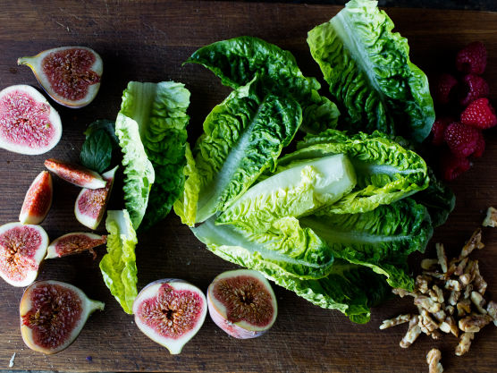 Skyll fikenene og skjær dem i båter. Skjær av rotenden på salaten og del bladene fra hverandre. Bland sammen fiken, salatblader, bringebær og godt med friske urter på et passende fat.