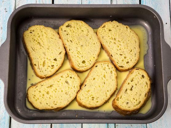 Legg brødskivene i et dypt fat eller i en ildfast form.  Hell egg- og melkerøren over brødskivene. Snu skivene et par ganger så de blir godt dekket. La dem stå og trekke til seg egg- og melkerøren i et par minutter.