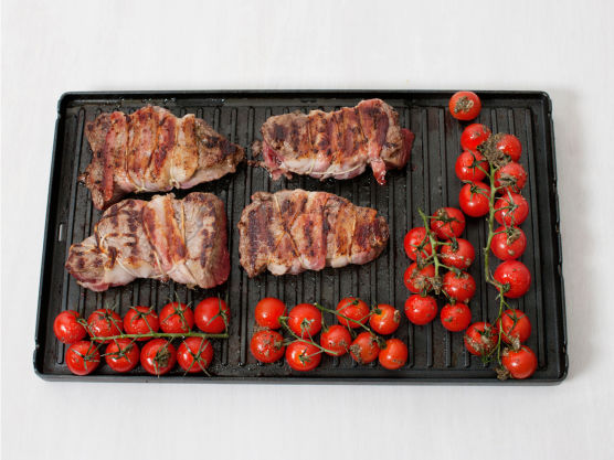 Grill eller stek baconbiffene på sterk varme, ca. 2-4 min. på hver side. Grill tomatene hele, ca. 3. min. Server biff, med grillede tomater og poteter med urteoljen.