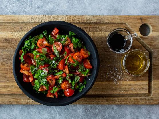 Bland tomatene sammen med grovhakket basilikum, en klunk olivenolje, noen dråper balsamicoeddik, en klype salt og kvernet pepper.