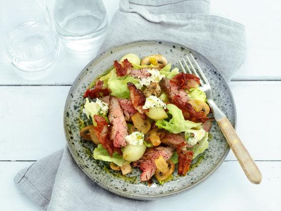 Klipp gressløk og bland inn i rømmen. Vask salaten og la den renne av. Fordel salatblader på tallerkener. Legg opp kjøtt og bacon, løk og sopp.