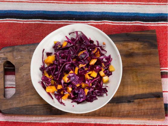 Finsnitt rødkål så tynt du klarer og skjær mango i terninger. Bland sukker og eddik, og bland dette med kål og mango.