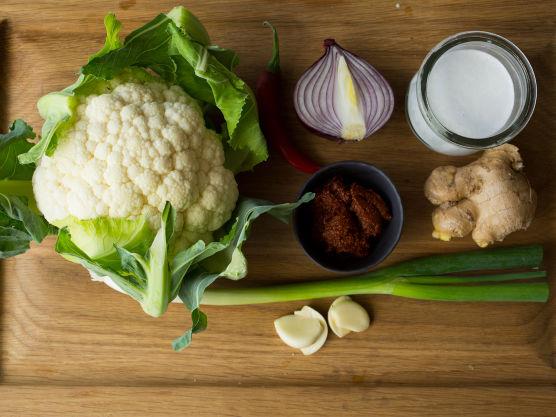 Rens og skjær løken i tynne skiver. Finhakk chilien. Skrap skallet av ingefæren med en teskje. Riv (bruk den fineste siden av rivjernet) eller finhakk ingefær og hvitløk, og rens og del blomkålen i buketter.