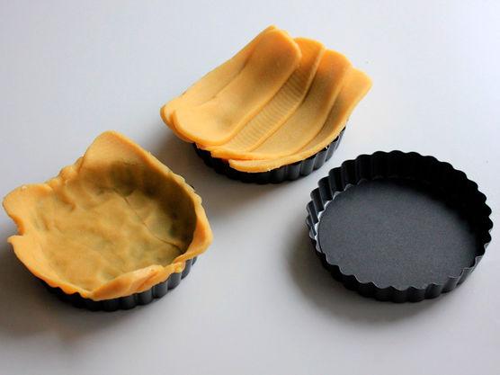 Skjær tynne strimler av paideigen som du legger i paiformen din slik at de overlapper hverandre. Bruk så hendene dine til å presse deigen på plass i formen, bruk til slutt en kniv til å skjære bort den overflødige deigen. Du kan selvfølgelig også bruke en kjevle, og da er det lurest å legge deigen mellom bakepapir, så slipper man at deigen setter seg fast i både kjevle og bord til enhver tid. Pass på at du skjærer strimlene, eller kjevler deigen tynn nok.