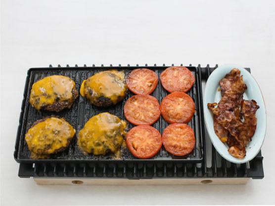 Grill eller stek hamburgerne på sterk varme, ca. 5 min. på hver side. Legg på cheddar og la osten smelte. Grill eller stek tomater på en side og baconet til det er gyllent, ca. 4 min.