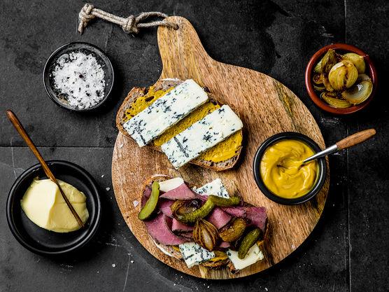 Smør skivene med smør og sennep, og legg to skiver ost på hver brødskive. Topp den ene brødskiven med roastbiff, glaserte småløk og små sylteagurker.