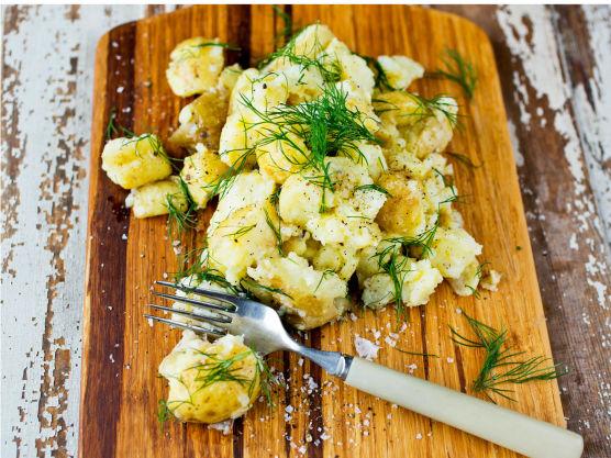 Bruk en gaffel og knus potetene grovt. Bland de knuste potetene med sitronsaft, olivenolje, grovhakket dill, en god klype salt og litt kvernet pepper.