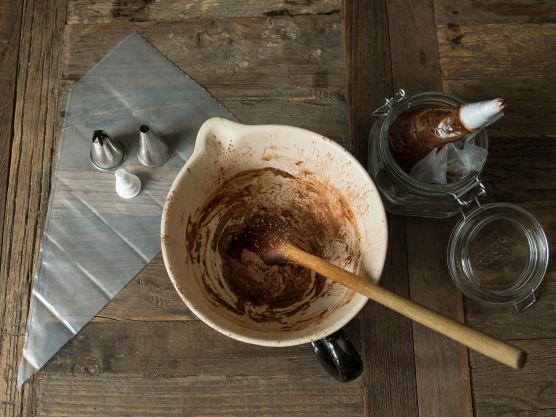 Til sjokoladekremen piskes først romtemperert smør og melis til smørkrem. Pisk inn eggeplommer, kakao og vann. Avkjøl kremen i kjøleskapet litt, slik at den får fin smørbar konsistens.