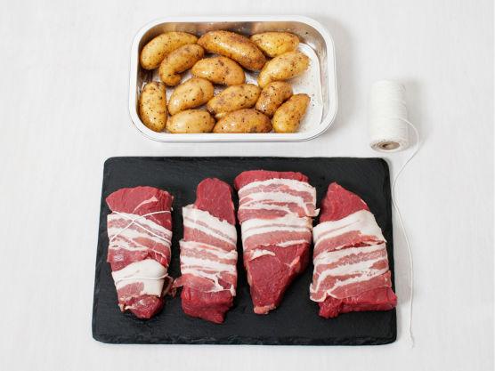 Grill potetene møre, eller stek i ovnen på 250C ca. 20 min. Surr bacon rundt biffene og fest med en grillpinne eller hyssing. Husk at MENY også tilbyr biff ferdigsurret i bacon.