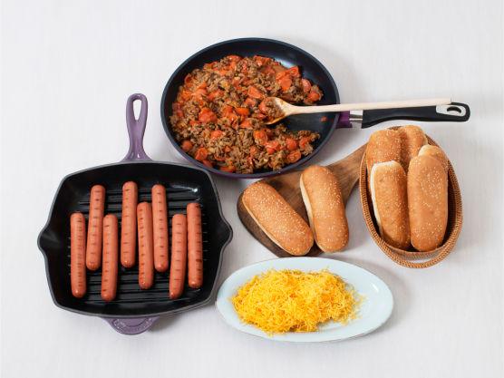 Varm pølsebrødene på grillen eller i ovnen på 200 °C. Ha pølsene i brød, topp med chili- og kjøttdeigblandingen, dryss over revet ost og server.