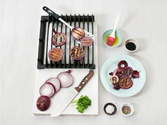 Skær løken, med skall, i tykke skiver. Pensle med olje og grill eller stek løkskivene, ca. 5 min. på hver side. Fjern skallet, ha over eddik og olje og krydre med salt og pepper. Hakk koriander og strø over.