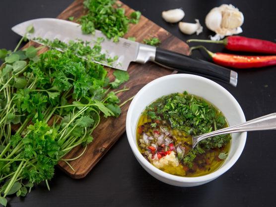 Finhakk alle urtene, rødløken og chilli. Bland med olivenolje, rødvinseddik og presset hvitløk. Smak til med salt og pepper.
