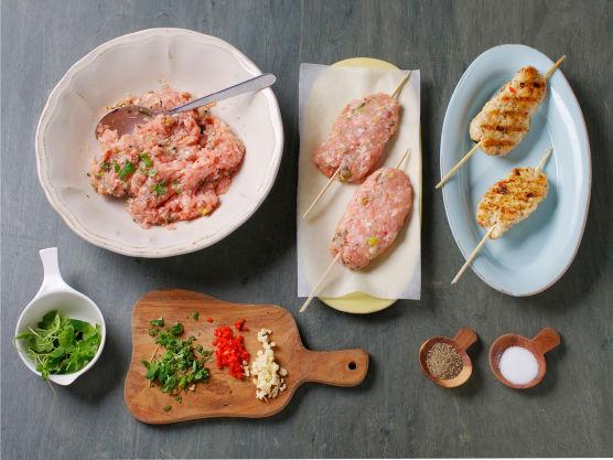 Finhakk hvitløk, oregano og chili, grovhakk nøttene og bland med kyllingkjøttdeig. Klem lange boller rundt grillpinner, og stek dem i en grillpanne, ca. 3 min. på hver side. Krydre med salt og pepper.
