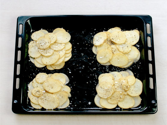 Høvle potetene i tynne skiver, pensle en langpanne med olje og ha i potetskivene. Strø over salt og pepper. Stek i ovnen på 200 °C ca. 20 min.