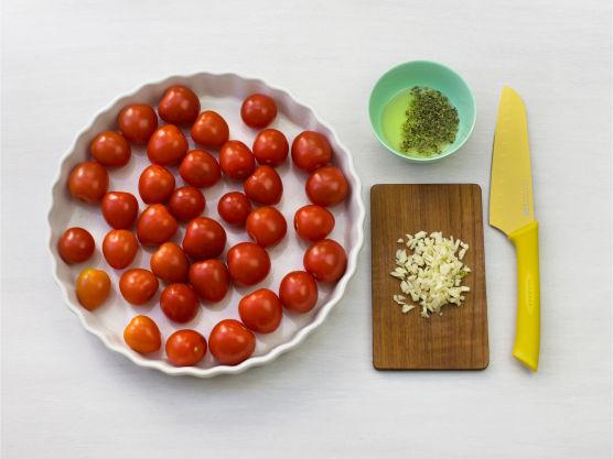 Ha tomatene i en paiform. Finhakk hvitløk, bland litt olje med oregano, og ha over tomatene. Stek i ovnen på 225 °C i ca. 10 min.