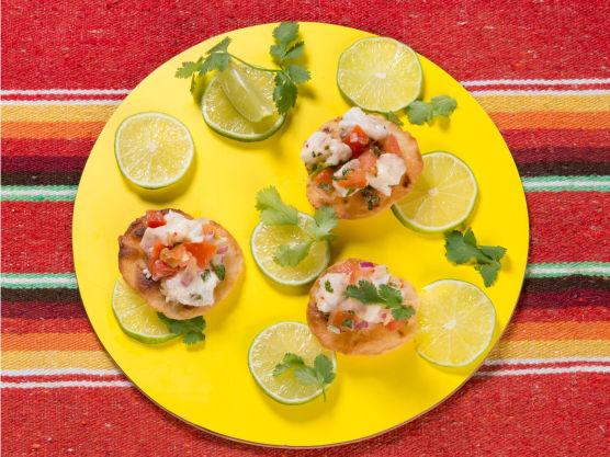 Legg kveitesalaten på de sprø tortillaene og pynt med ekstra koriander og noen limebåter.