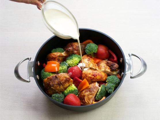Ha kylling og grønnsaker i en dyp stekepanne, tilsett tomater og fløte i kyllinggryten.
