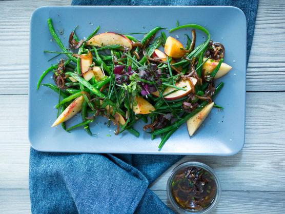 Del ferskenene i jevne biter eller båter. Bland sammen aspargesbønner og fersken, drypp over dressingen og pynt med grovhakket gressløk.