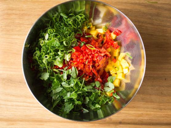 Fjern skinn og kjerner og skjær paprika og chili i små biter. Skrell og skjær mangoen i små terninger og finsnitt vårløken. Bland sammen paprika, chili, mango og vårløk.