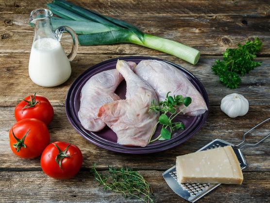 Salte og pepre kyllingstykkene og legg dem i en ildfast form. Skjær purren i skiver og tomaten i terninger. Fordel dem rundt kyllingen i formen.
