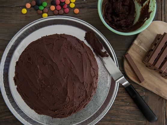 Legg den ene kakebunnen på et fat. Legg et lag sjokoladekrem på før du legger på det andre laget.