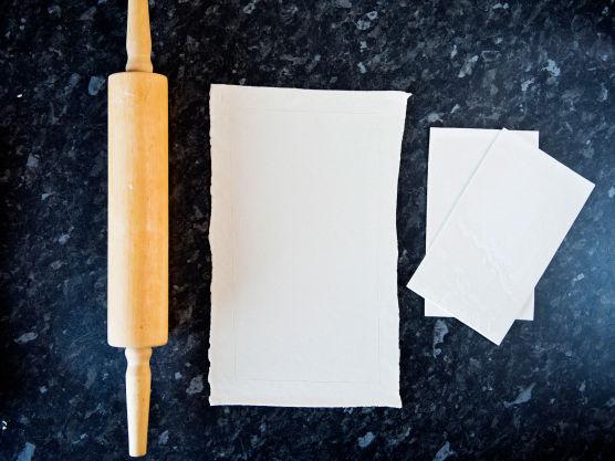 Legg platene oppå hverandre og kjevl de ut til et rektangel (på et melet bakebord). Løft butterdeigen over på et stekebrett dekket med bakepapir.