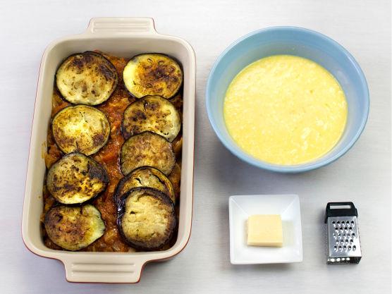 Riv parmesan og bland med egg, ost og melk i en bolle. Skjær aubergine i skiver, stek gylne i olje i en stekepanne og legg lagvis med tomatsaus i en smurt ildfast form.