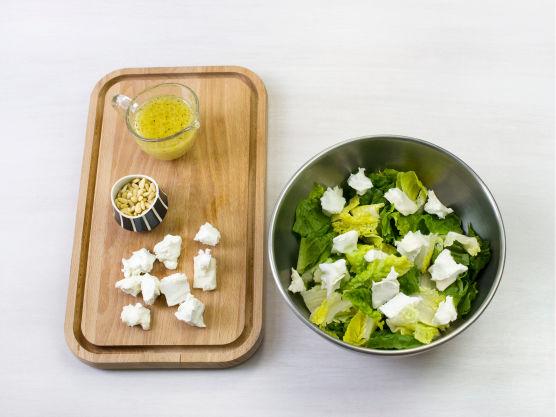 Vask og riv salat i biter, del og ha i chèvre, bland inn vinaigrette, dryss over pinjekjerner og server.
