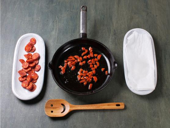 Skjær chorizo i terninger, sprøstek på middels varme og la renne av på tørkepapir. Dryss over fisken og server.