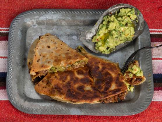 Brett tortillaen over til en halvmåne og klem godt ned. Stek i oven på 220 grader i 4–5 min eller i en tørr panne på begge sider til osten er smeltet. Kutt i kakestykker og server gjerne med flere typer salsa, ekstra guacamole og rømme som dipp.