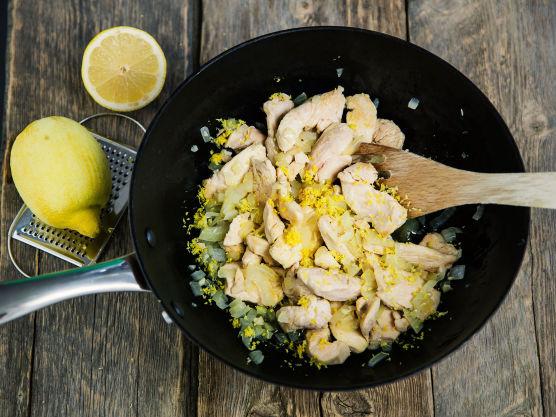 Stek kyllingstrimler, finhakket løk og finrevet sitronskall i olivenolje til kyllingen er godt brunet på alle sider.