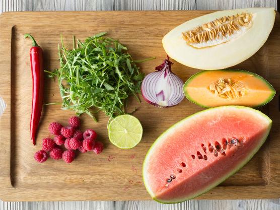 Rens melonene for kjerner og skjær av skallet. Del melonkjøttet i jevne biter og bland melonbitene sammen med ruccula og bringebær. Drypp over 1/3 av dressingen og server resten ved siden av.